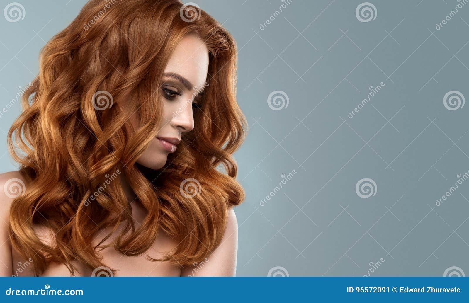 Rode haired vrouw met omvangrijk, glanzend en krullend kapsel Kroeshaar