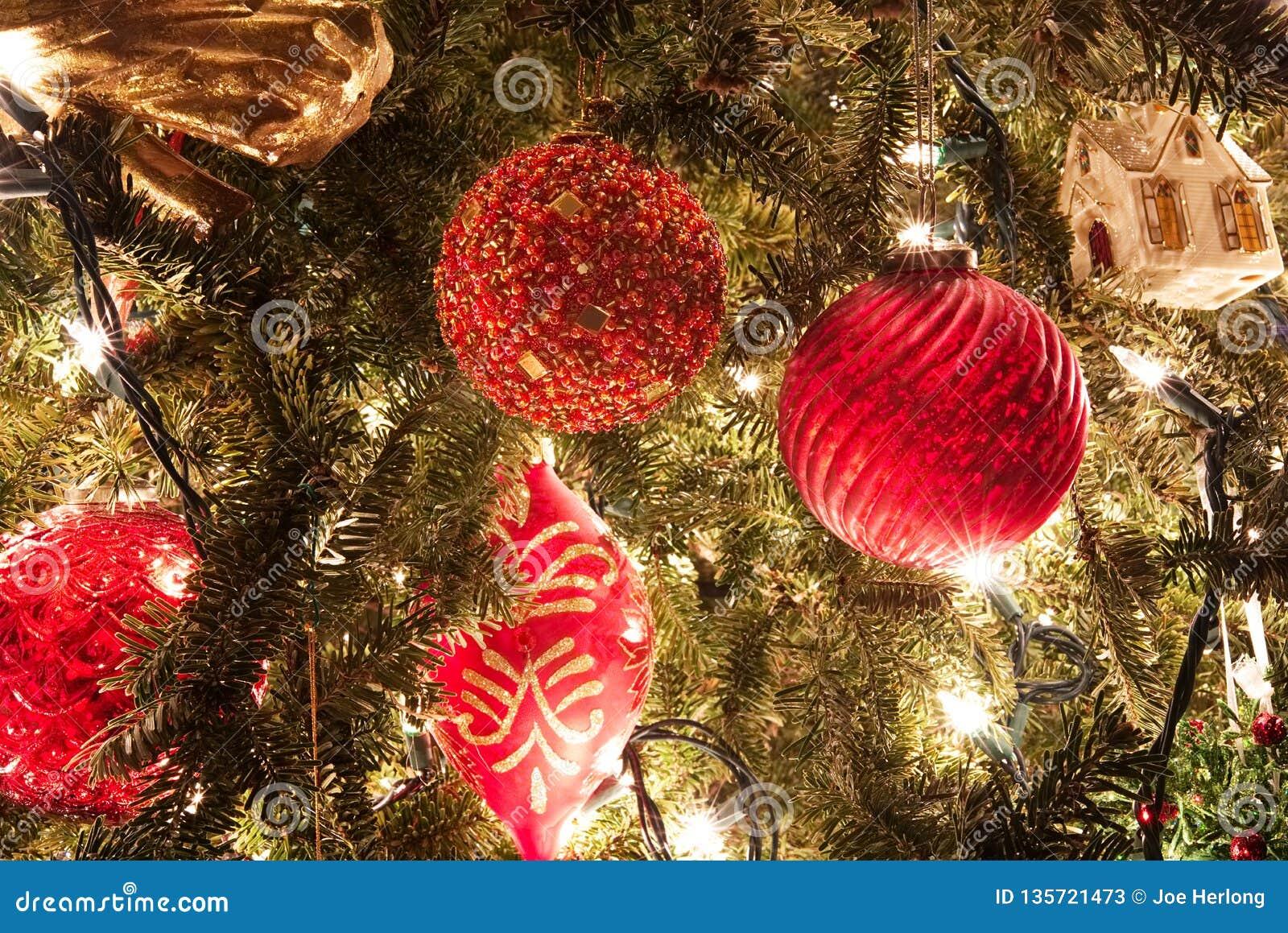 Rode Kerstmis siert het hangen op een boom met vage lichten op de achtergrond