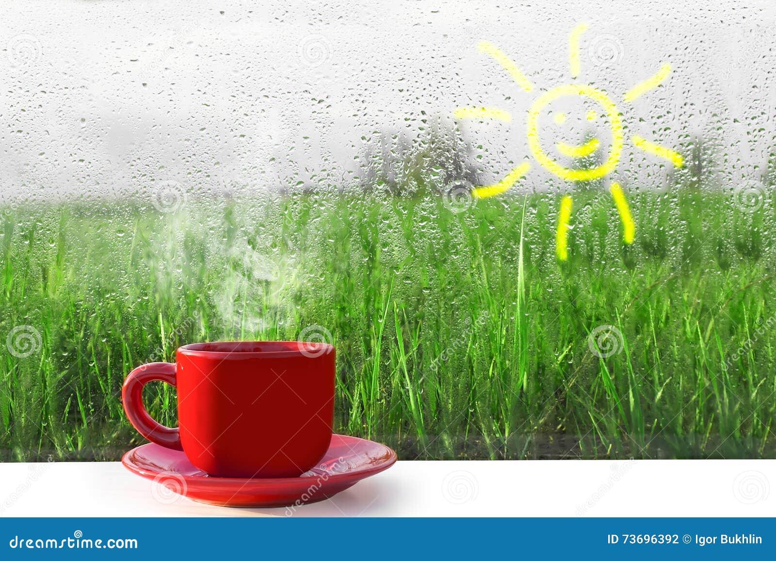 Rode Kop van hete koffie op de lijst De mening van het venster op aard Regen buiten het venster