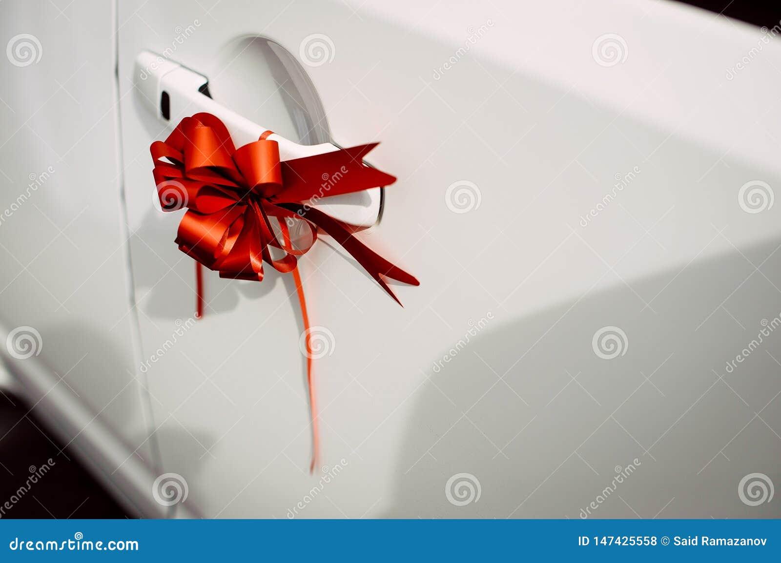 Rode lintboog op het deurhandvat van een witte auto