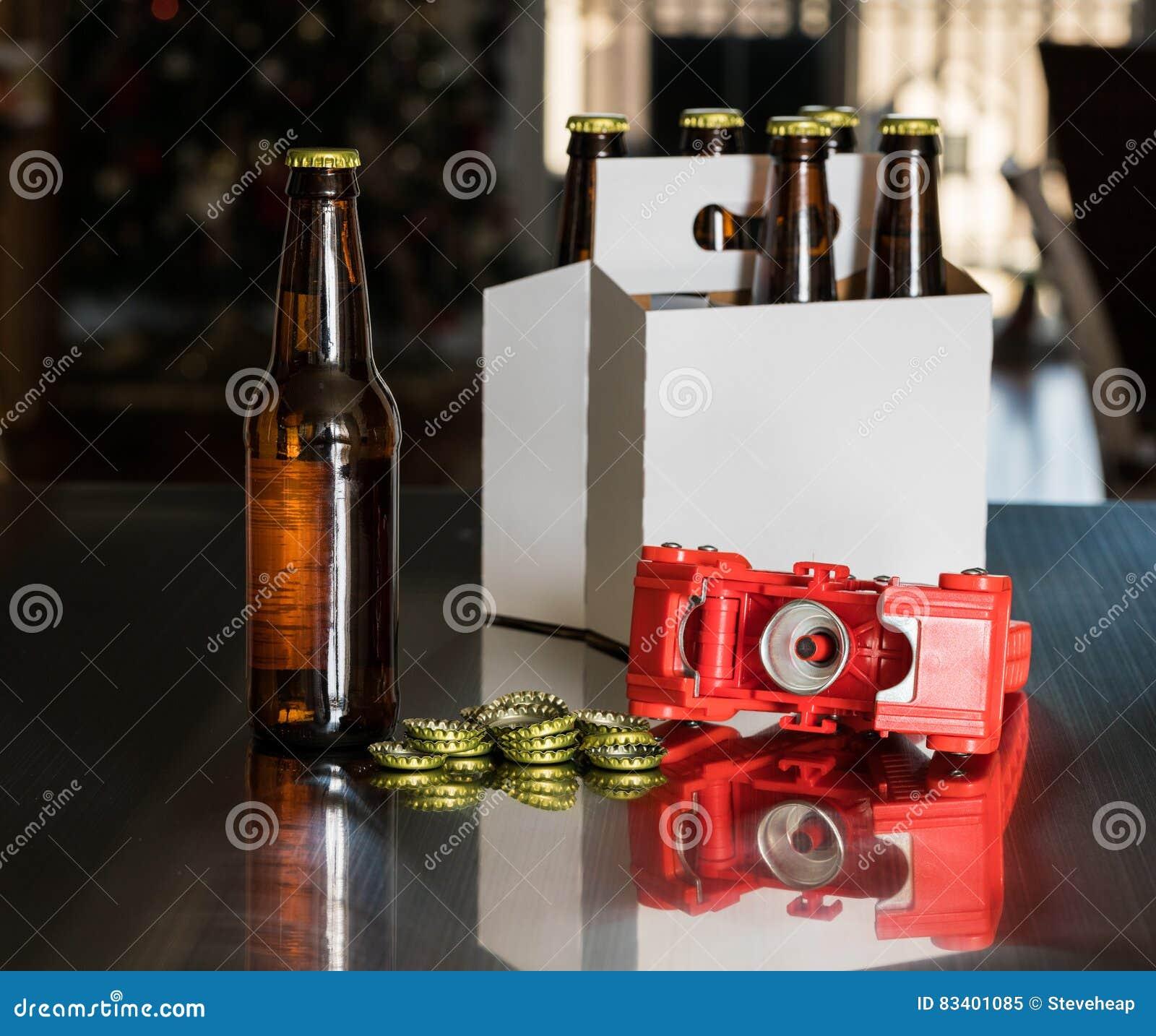Rode plastic capsuleermachine om metaalkappen op bierfles te zetten