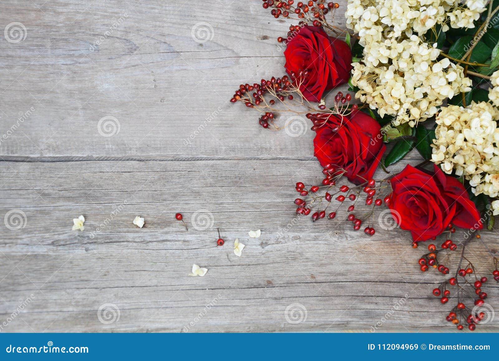 Rode rozen, hydrangea hortensia, heupen op houten achtergrond