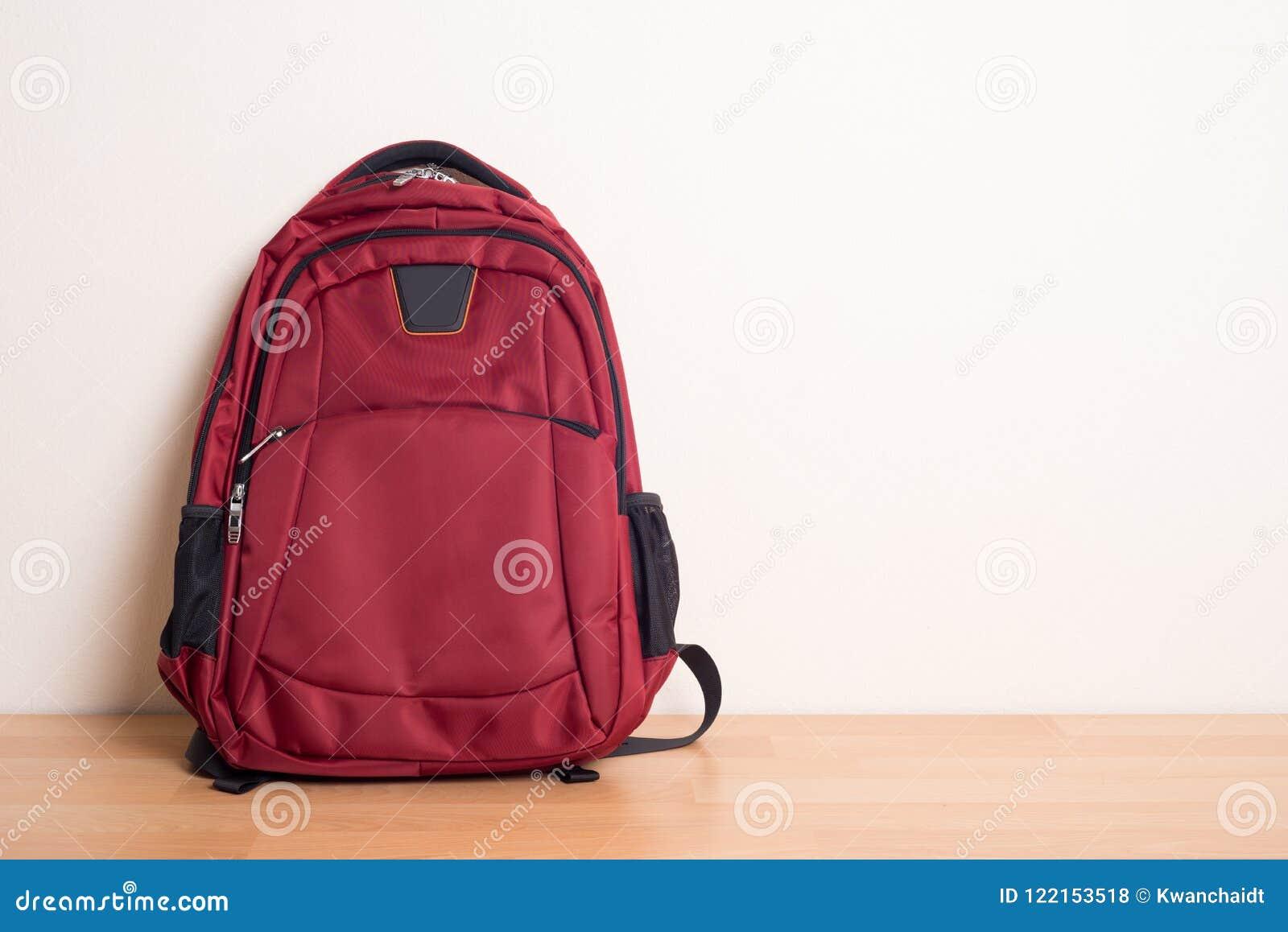 Rode schooltas op houten lijst