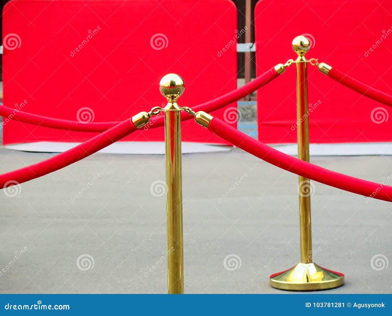 Rode tapijtingang met gouden stangen en kabels Beroemdheidsbenoemden aan première Sterren op het feestelijke toekennen van prijze