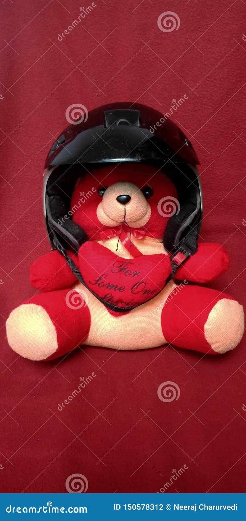 Rode teddybeer dragende helm in rode achtergrondvoorraadfoto