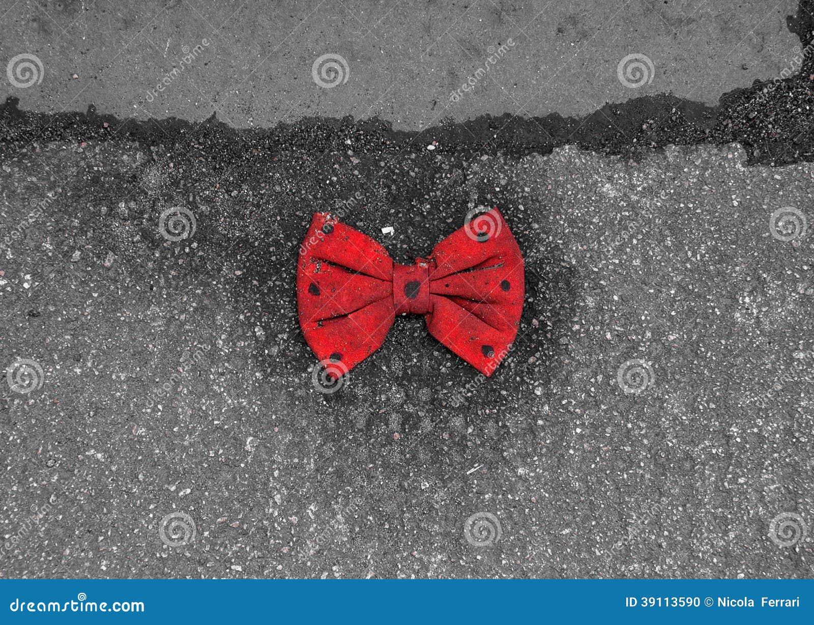 Rode vlinderdas die met zwarte punten op de bestrating liggen