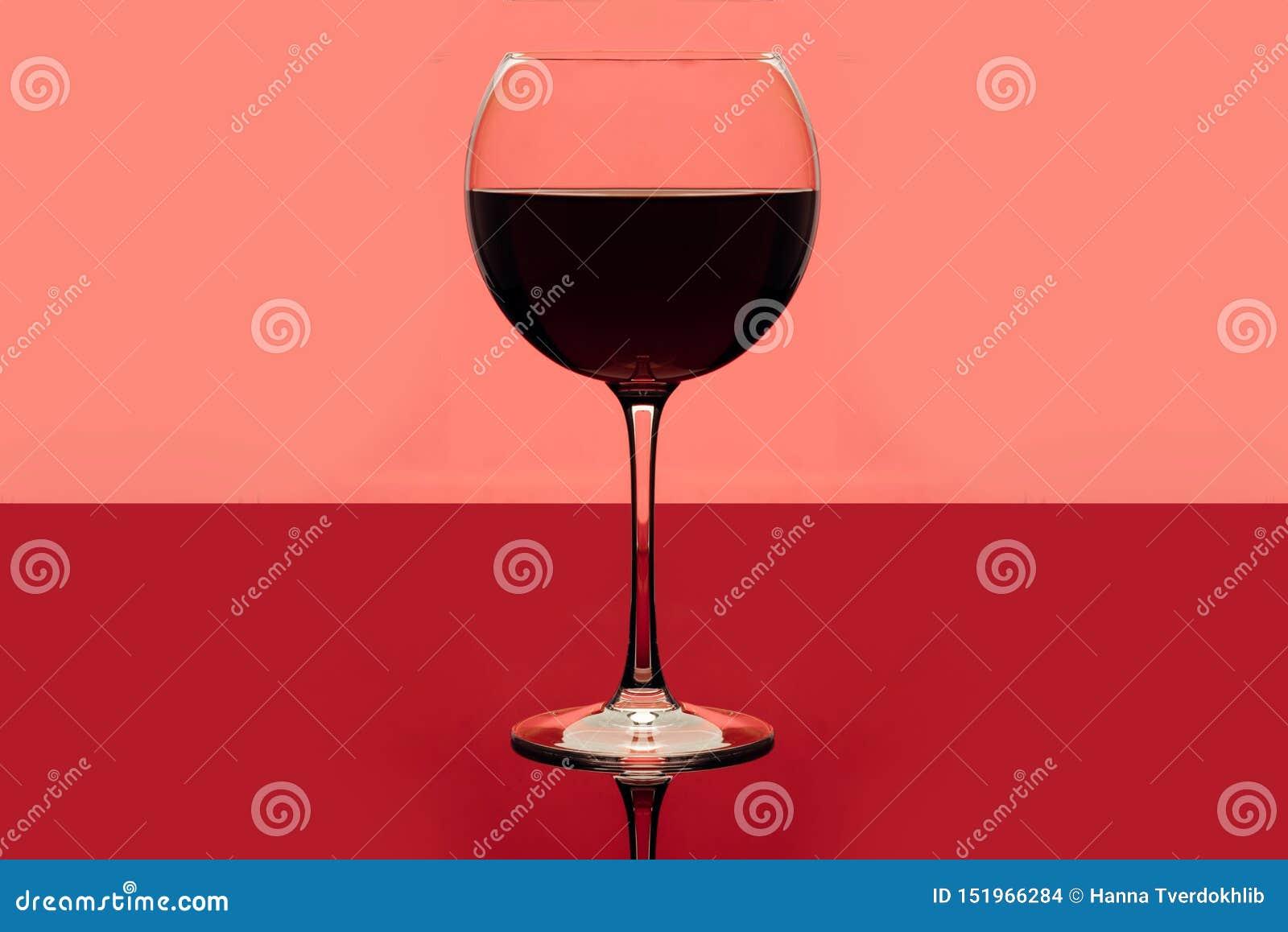 Rode wijn Drankglas rode wijn op een roze en rode achtergrond Alcoholische drank Romantische avond of eenzaamheid