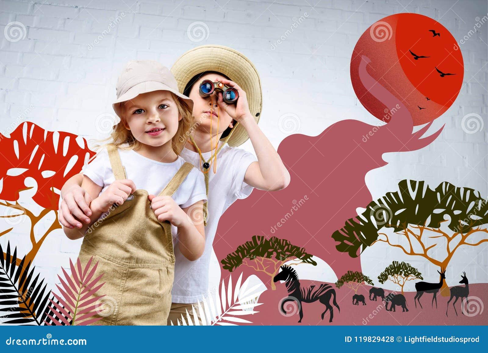 Rodzeństwa ściska i patrzeje w lornetkach przy zebrą w safari kostiumach, słonie