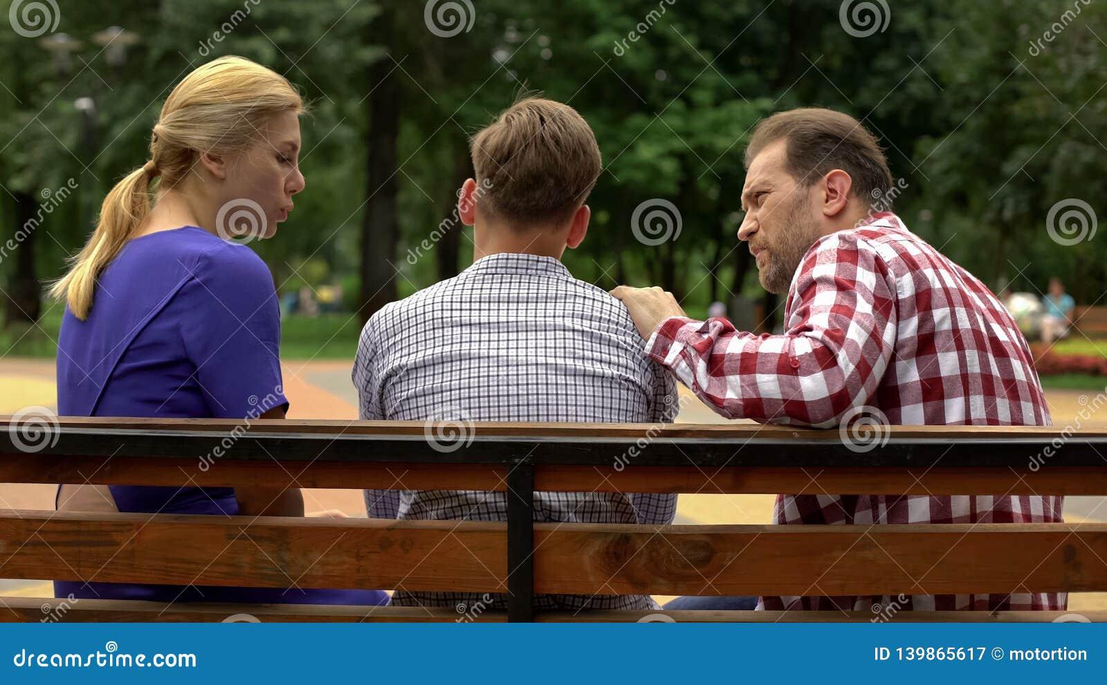 Rodzice opowiada z synem na ławce w parku, wspierać nastoletni w czasie kłopot