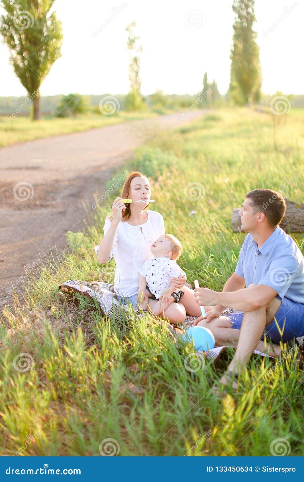 Rodzice siedzi na trawie z małego dziecka i dmuchania bąblami