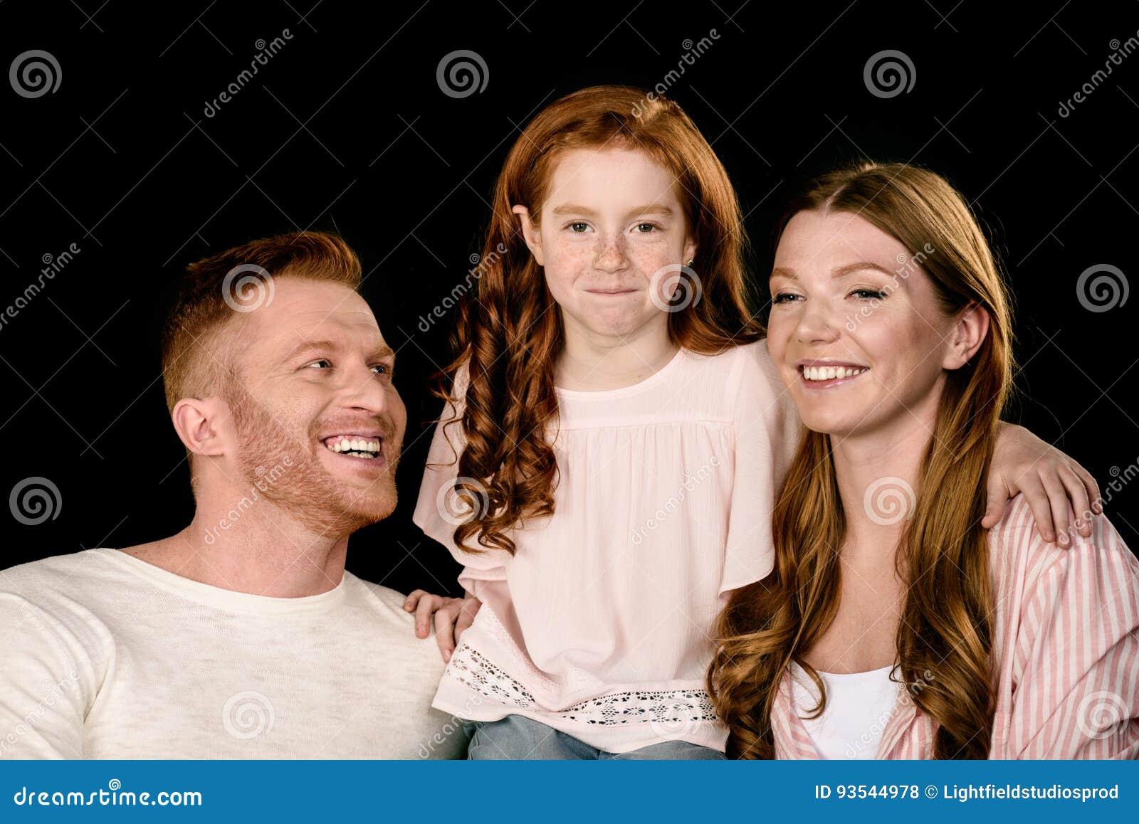 Rodzice z uroczą małą córką ono uśmiecha się i obejmuje odizolowywający na czerni