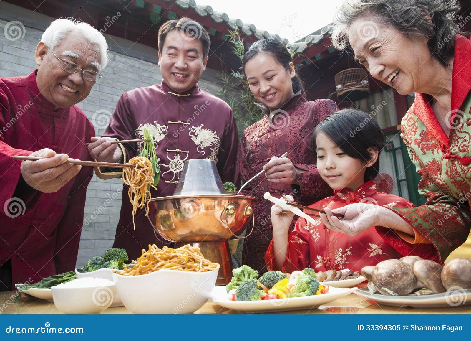 Rodzina cieszy się Chińskiego posiłek w tradycyjni chińskie odzieży