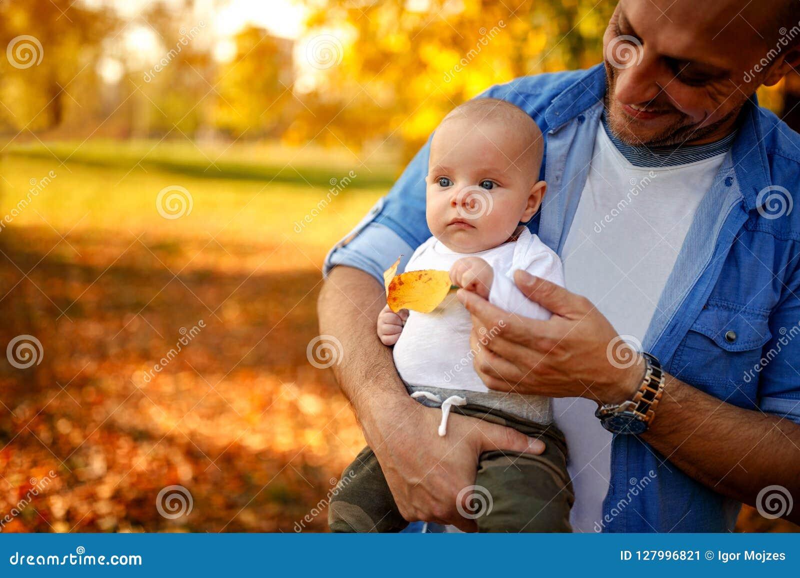 Rodzina cieszy się w jesień ojcu z dzieckiem