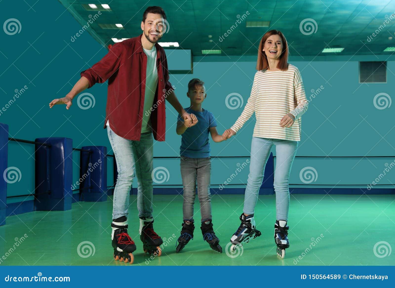 Rodzina ma zabawę przy rolkowym łyżwiarskim lodowiskiem
