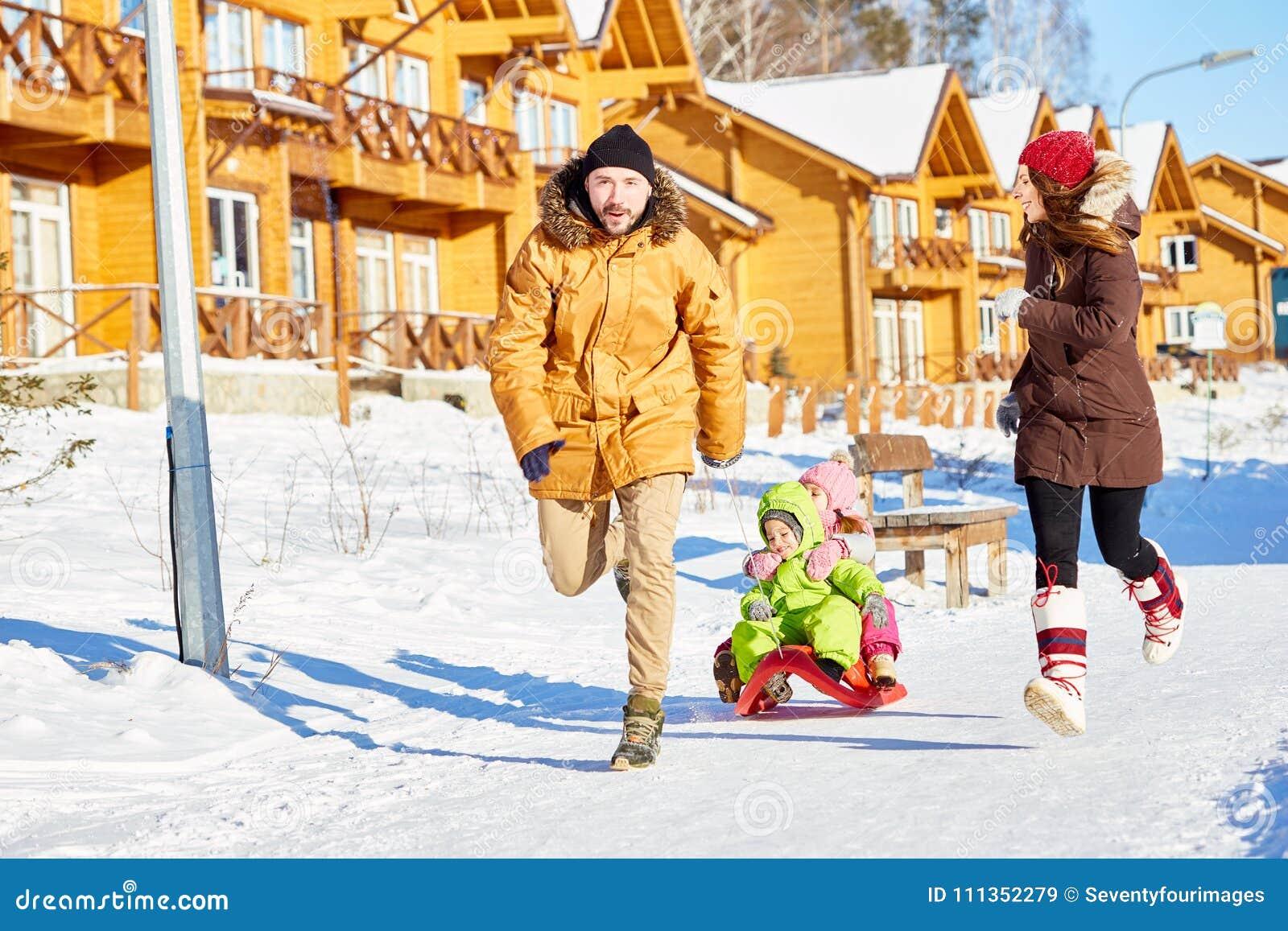 Rodzina ma zabawę w zimie