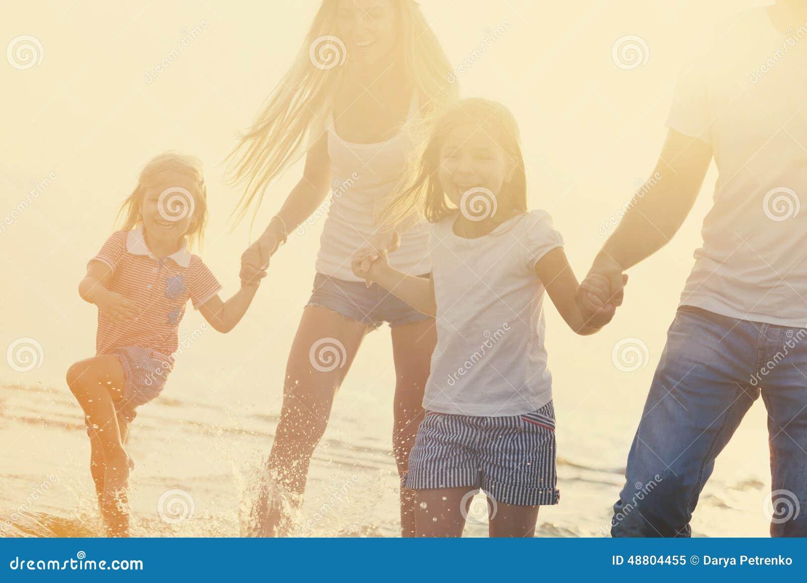 Rodzina ma zabawy runÑ 'ing na plaży przy zmierzchem