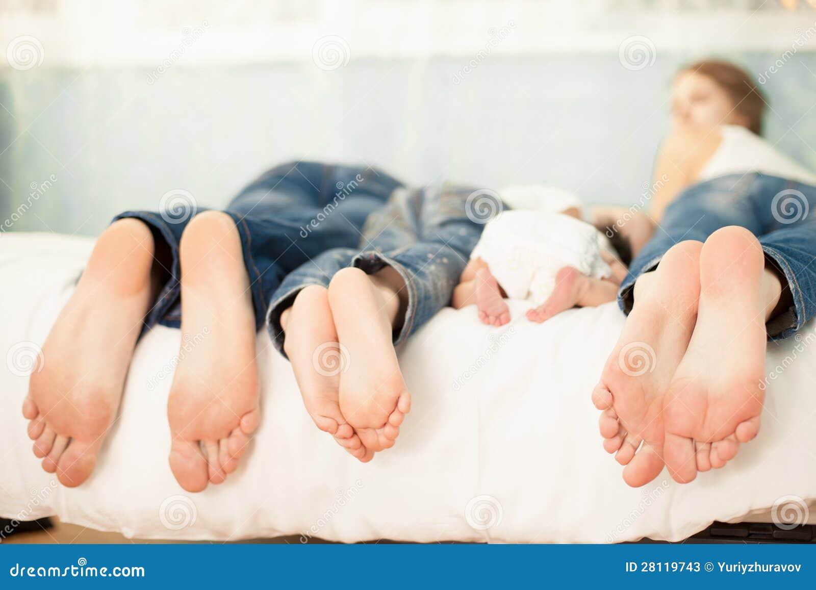 Rodzina na łóżku z ich cieków pokazywać w domu