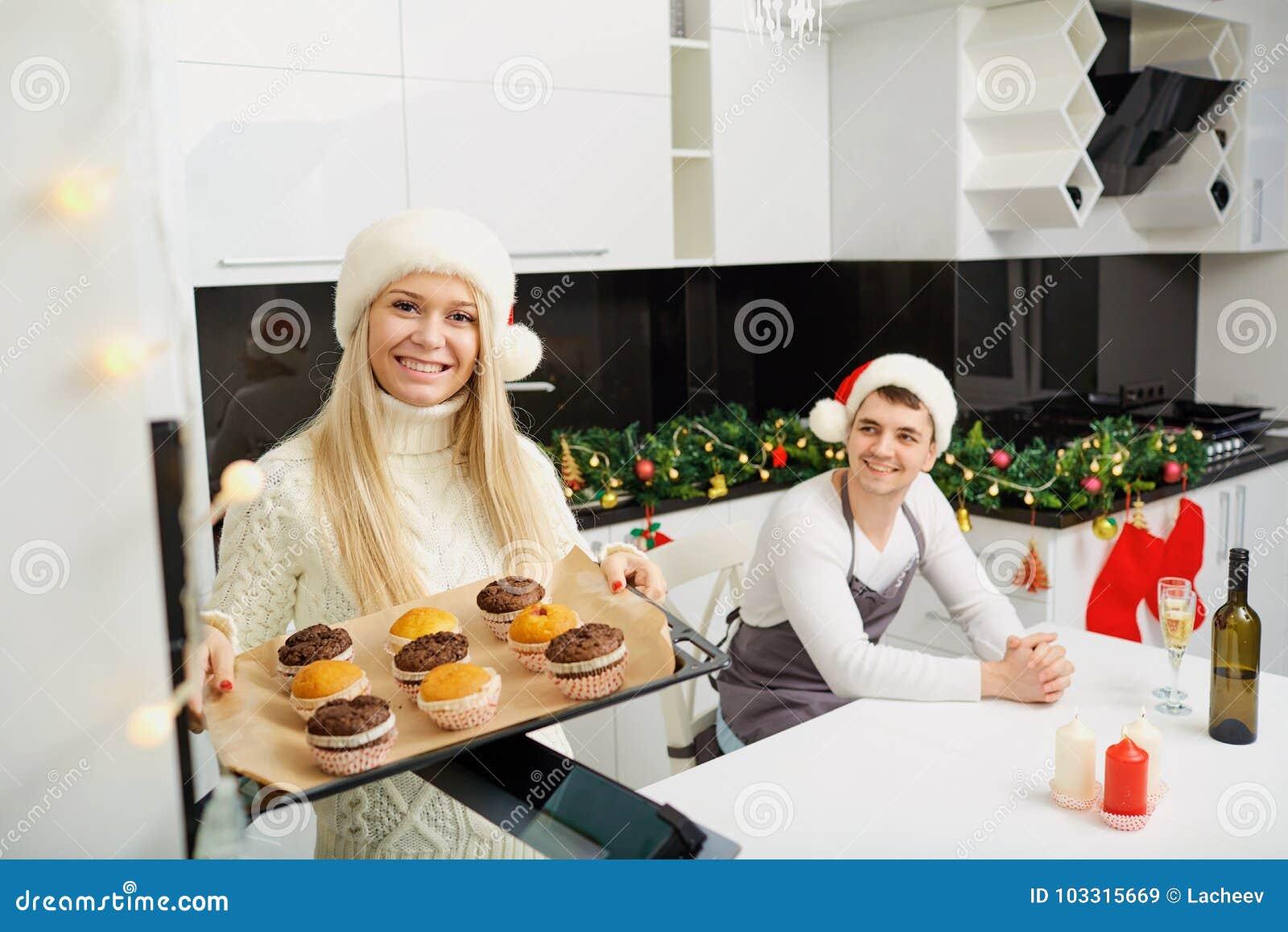 Rodzina piec babeczki na bożych narodzeniach w kuchni