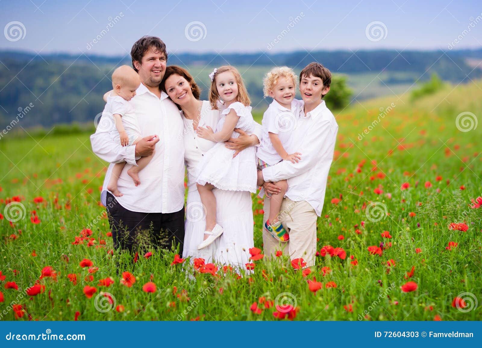 Rodzina z cztery dzieciakami w makowym kwiatu polu