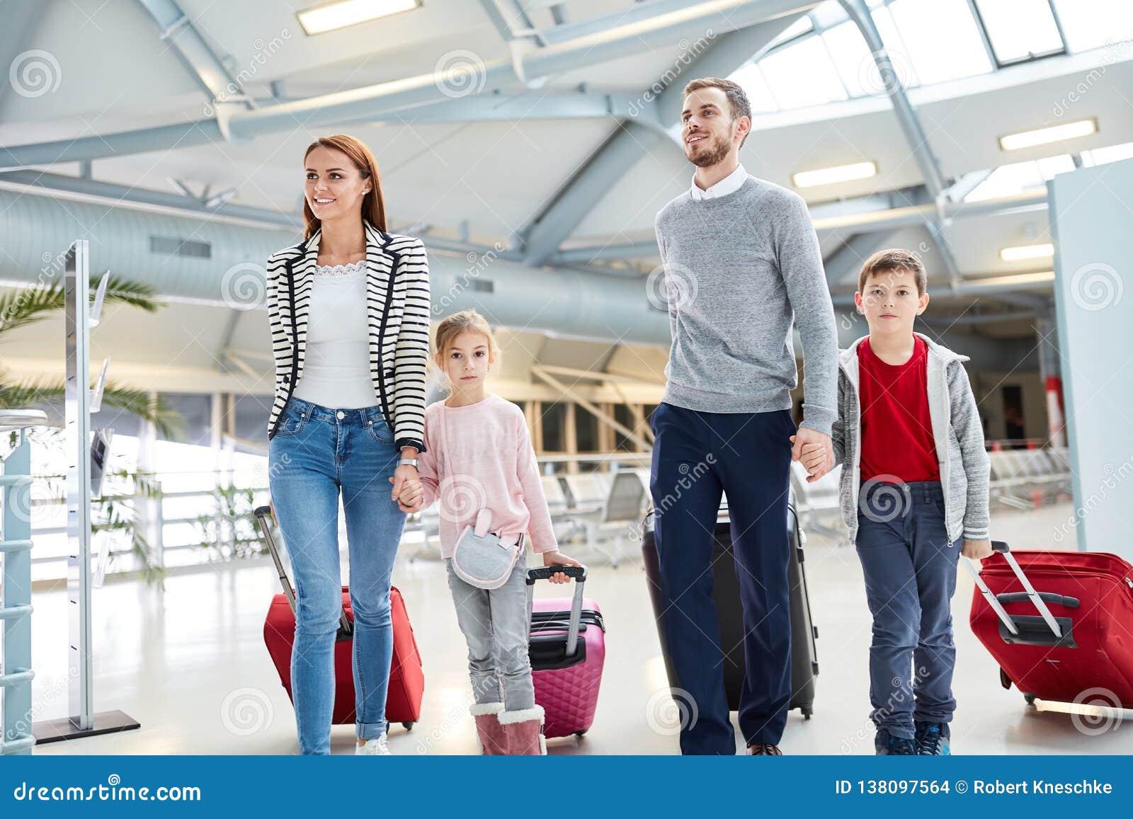 Rodzina z dziećmi i walizkami w lotnisku