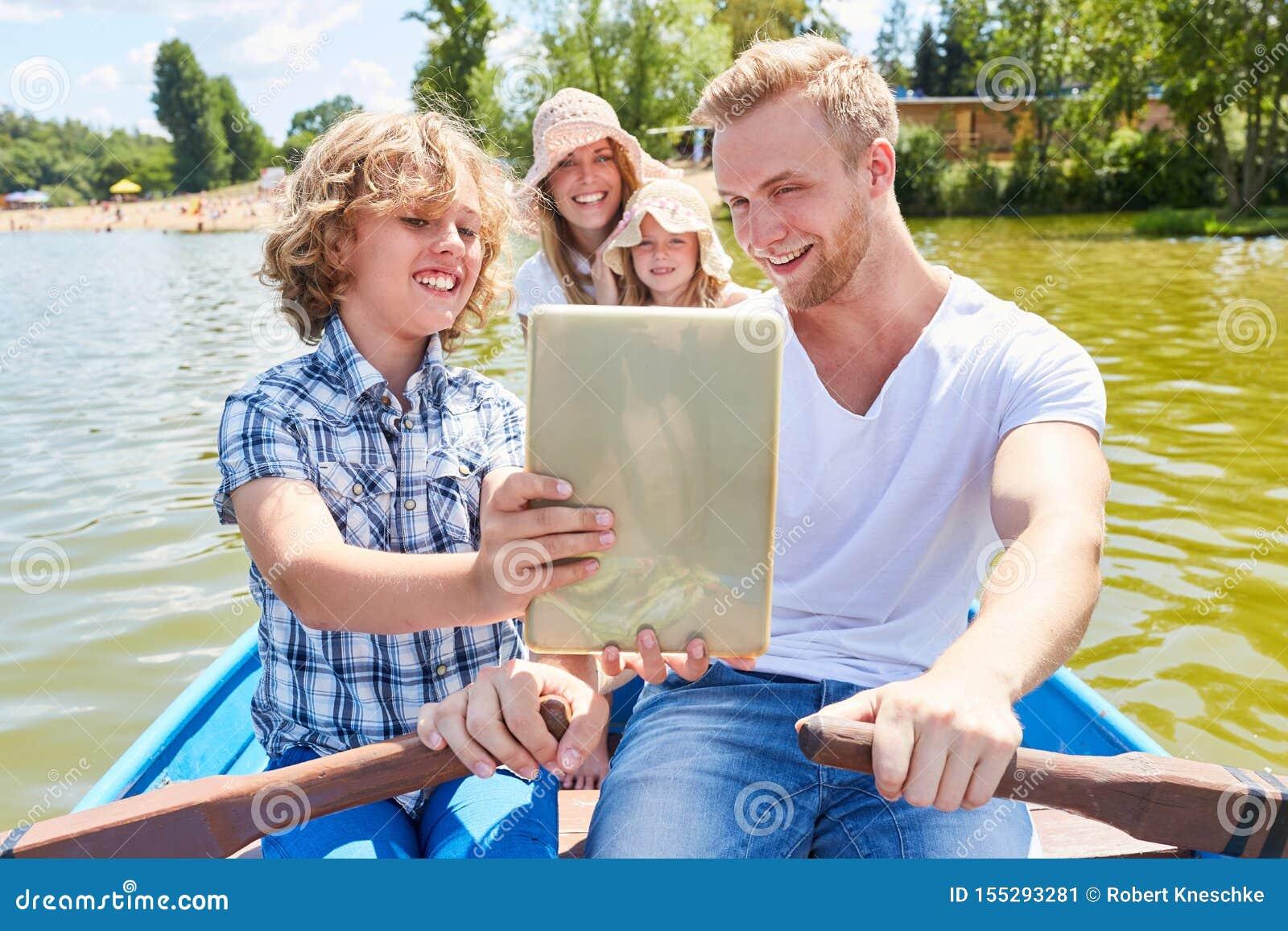 Rodzina z pastylka komputerem na łódkowatej wycieczce turysycznej
