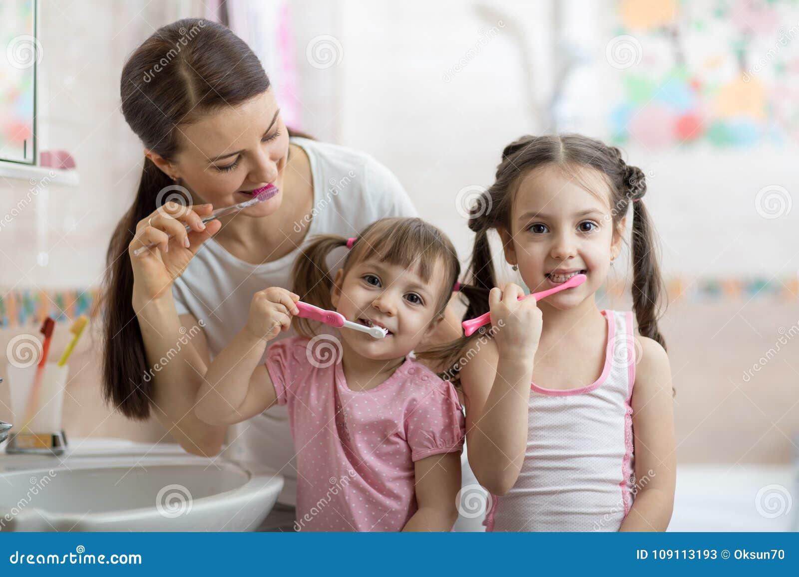 Rodzinna mama i dwa małej dziewczynki szczotkujemy ich zęby