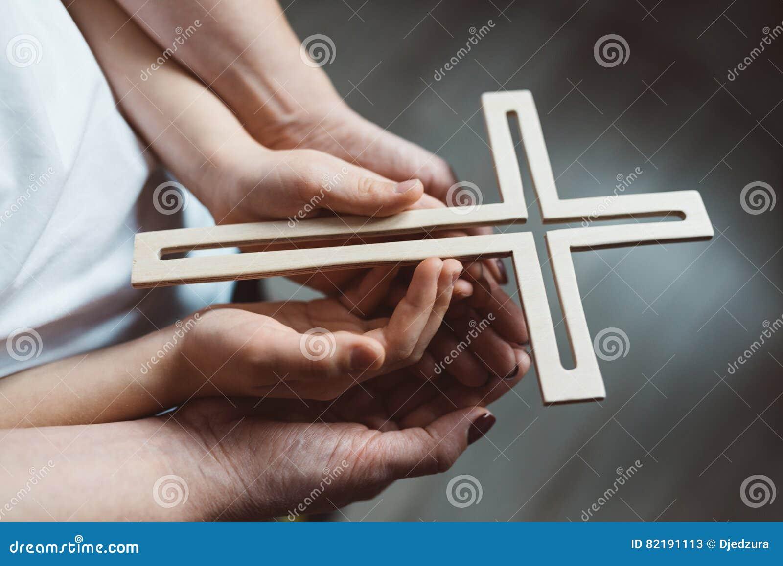 Rodzinna modlitwa z drewnianym krzyżem