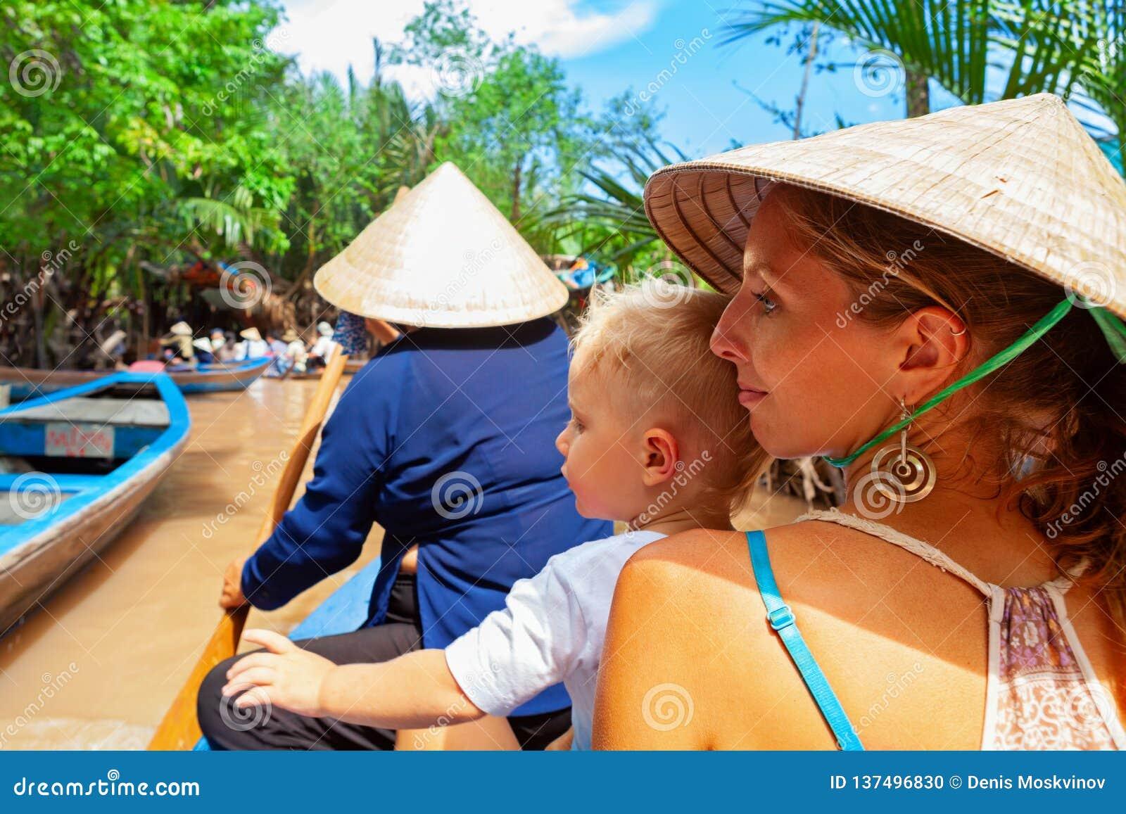 Rodzinna przejażdżka na tradycyjnej Wietnamskiej łodzi w Mekong rzeki delcie