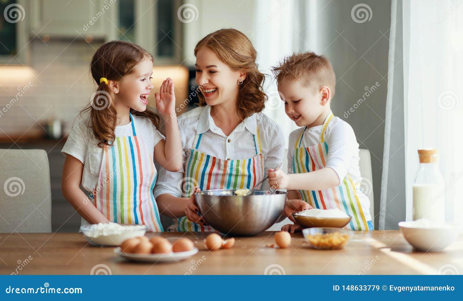 Rodzinna szcz??liwa kuchnia matka i dzieci przygotowywa ciasto, piec ciastka