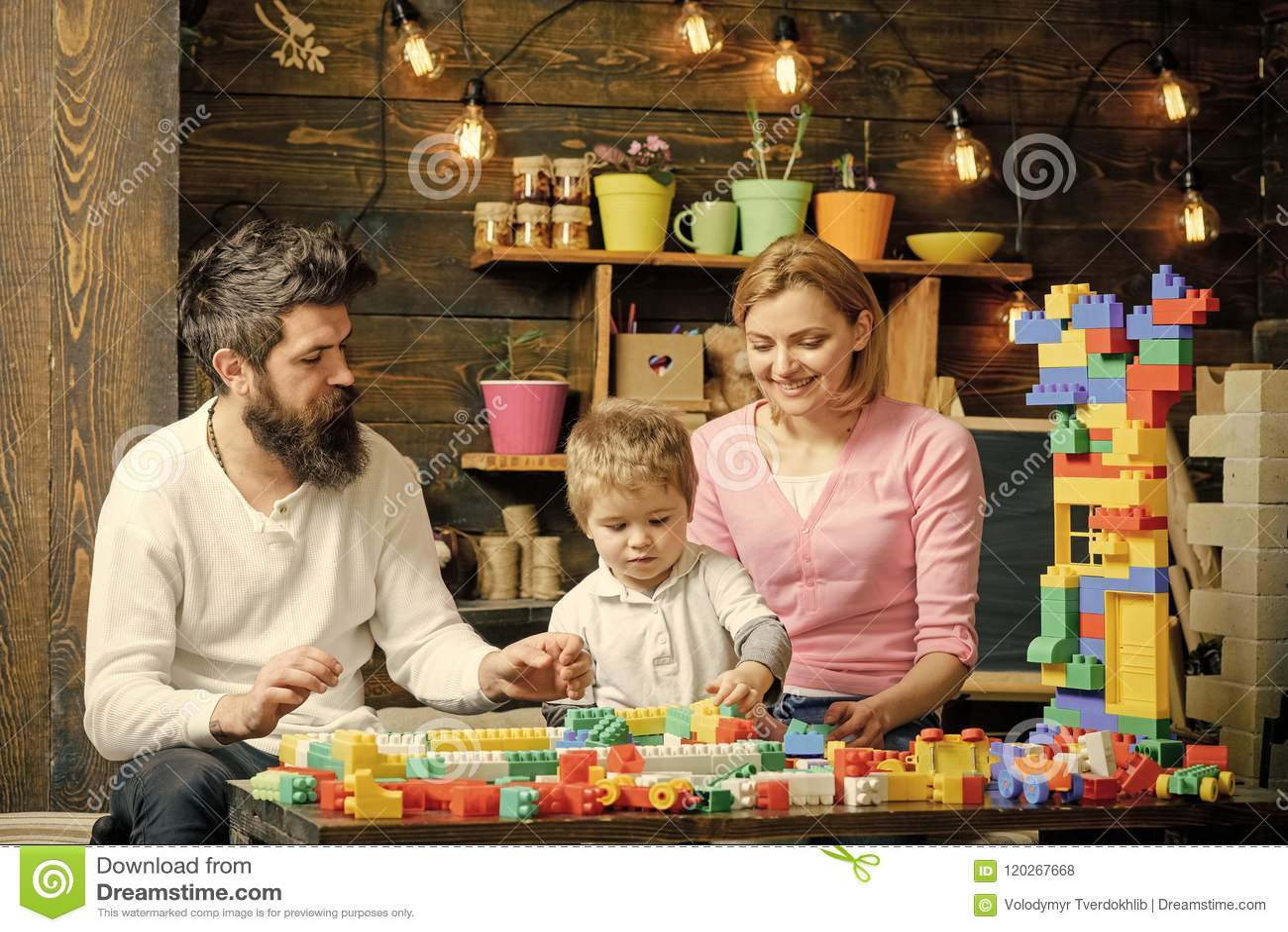 Rodzinne gry Ojcuje, matka i śliczna syn sztuka z konstruktor cegłami Rodzina na ruchliwie twarzach wydaje czas wpólnie wewnątrz