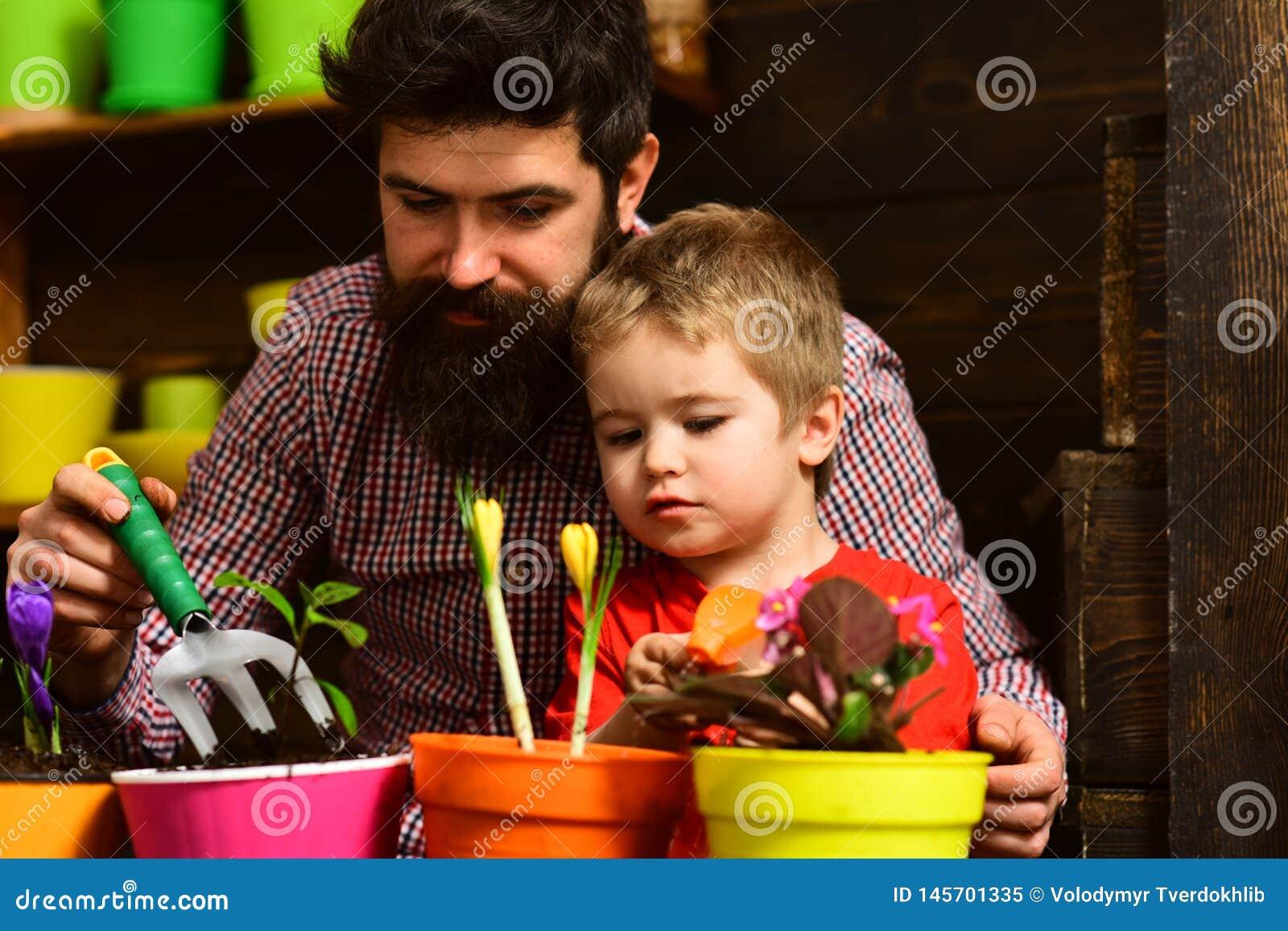 Rodzinny dzie? charcica Ojciec i syn Ojca dzie? Kwiat opieki podlewanie Glebowi u?y?niacze szcz??liwe ogrodniczki z wiosn?