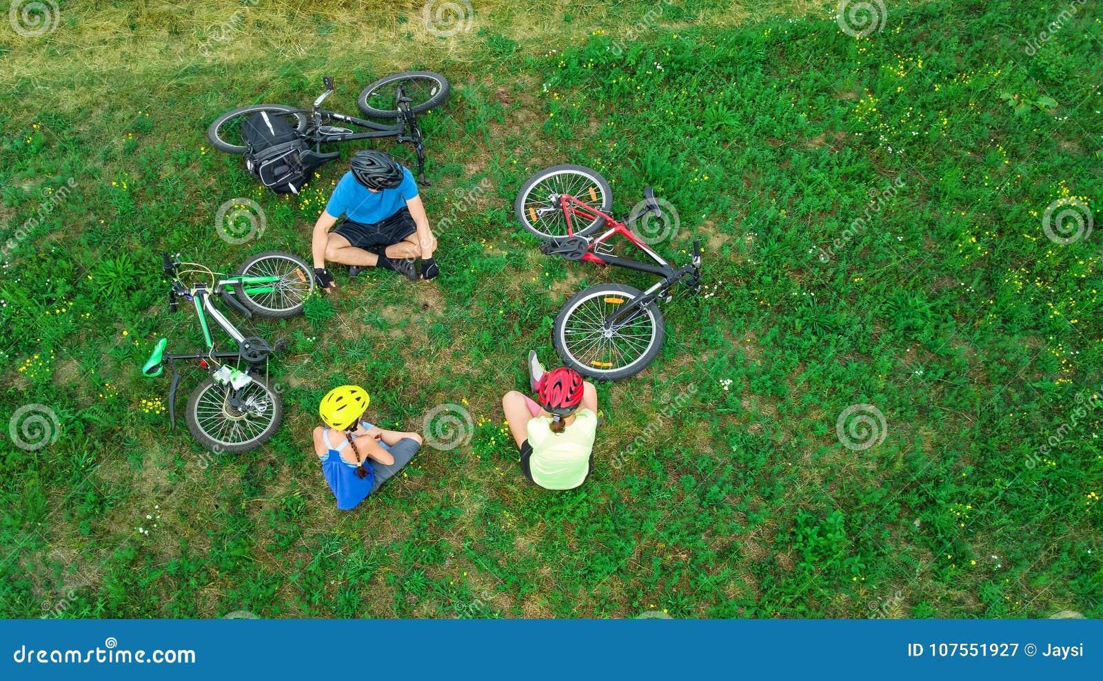 Rodzinny kolarstwo na rowerów outdoors widok z lotu ptaka od above, szczęśliwi aktywni rodzice z dzieckiem zabawę i relaksuje na