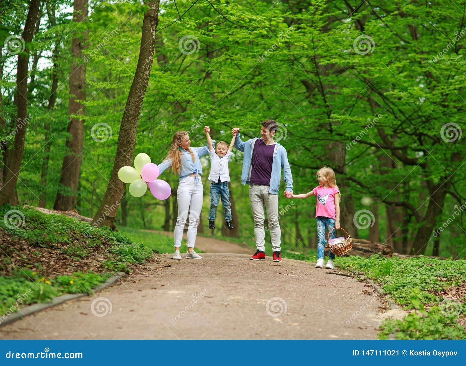 Rodzinny ojciec i matka z dwa dzieciakami chodzi w lato zieleni miasta parku na pinkinie, szcz??liwych wakacji rodzicach i dzieci