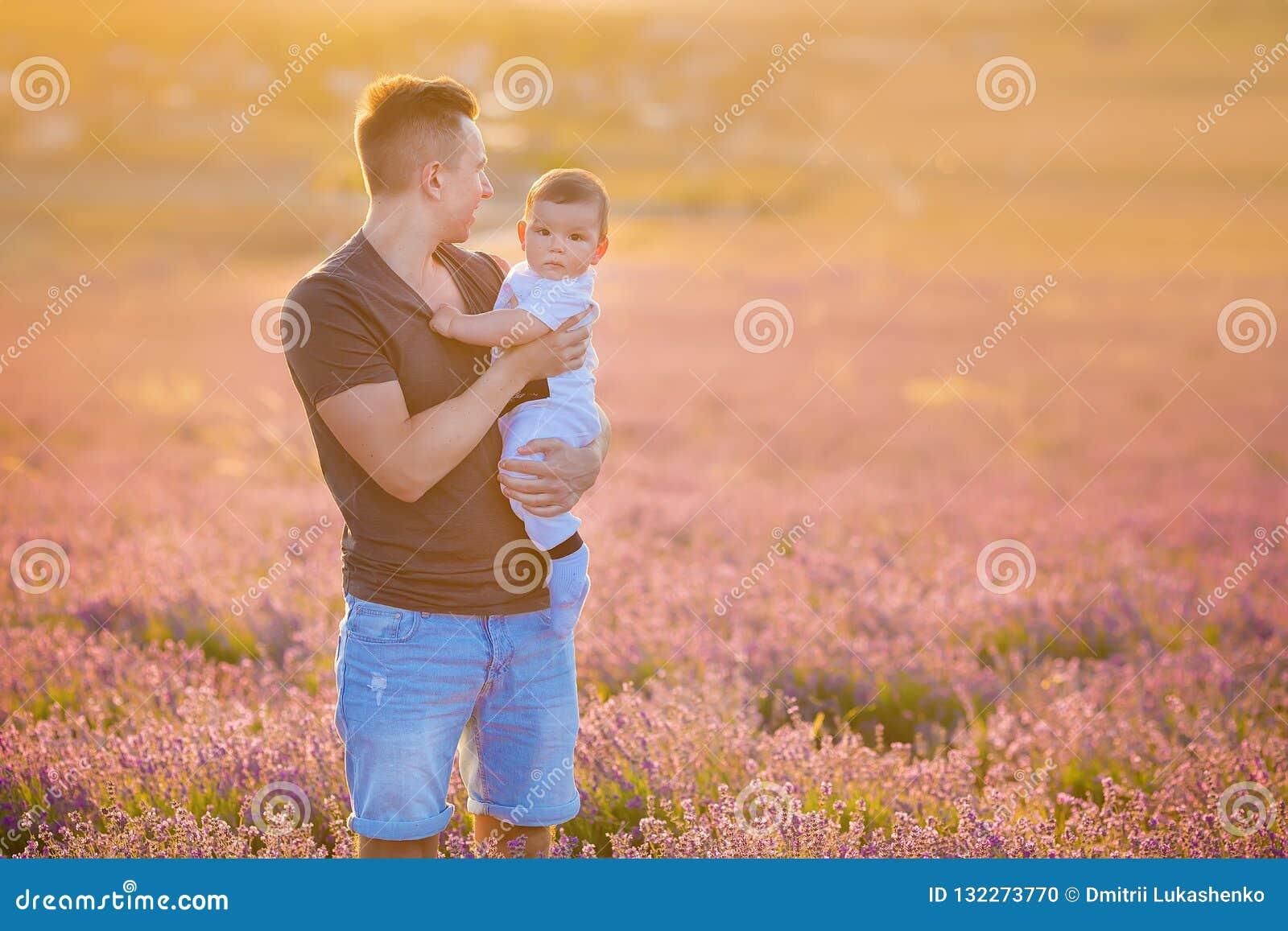 Rodzinny portret ojca mienia dziecka syn pozuje na lawenda śródpolnych jest ubranym niebieskich dżinsach koszulce i