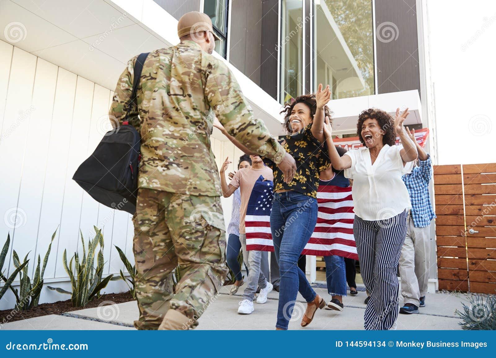 Rodzinny wita tylny millennial amerykanin afrykańskiego pochodzenia żołnierza oddawania dom, niskiego kąta widok