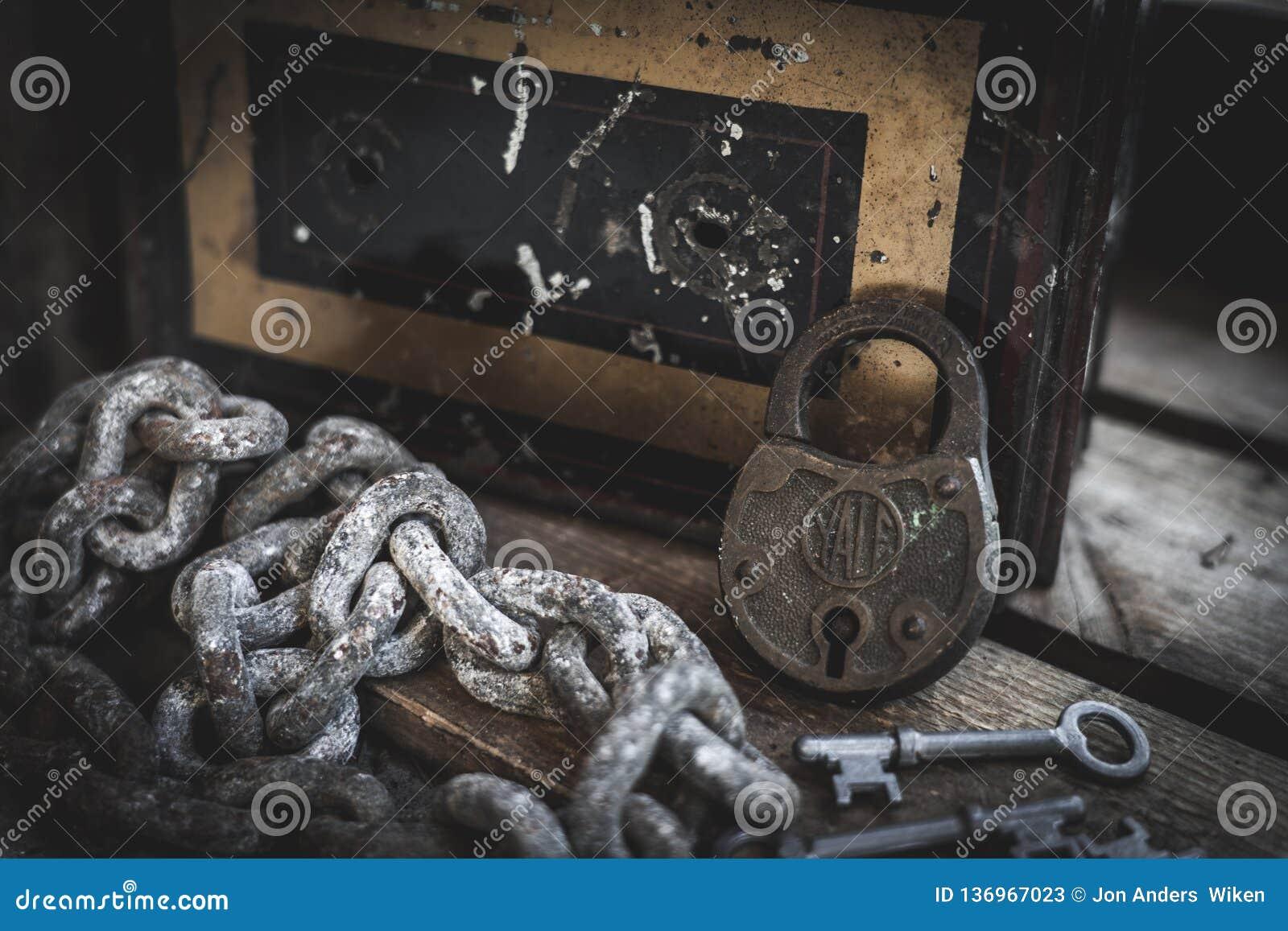 Roestig slot, sleutels, ketting en antieke doos in houten geval