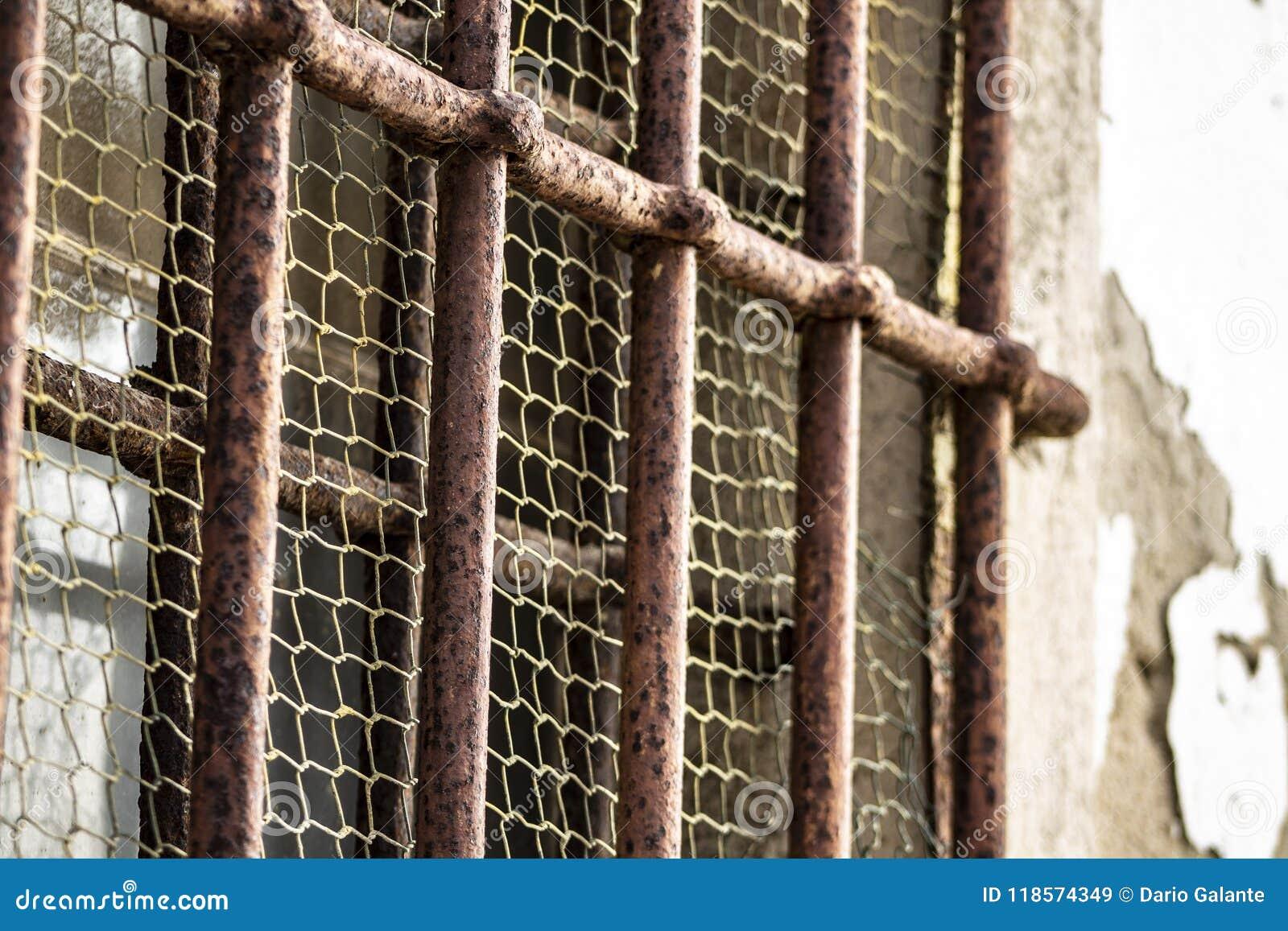 Roestige bars van een gevangenis