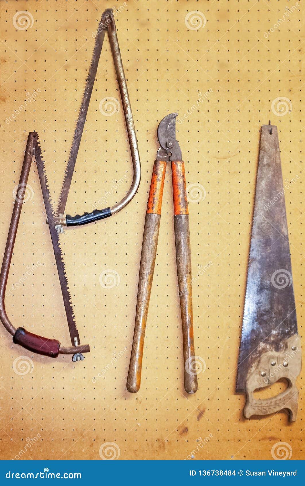 Roestige oude hulpmiddelen die op een pegboard in een woongarage met inbegrip van zagen en een lidmaatsnijder hangen