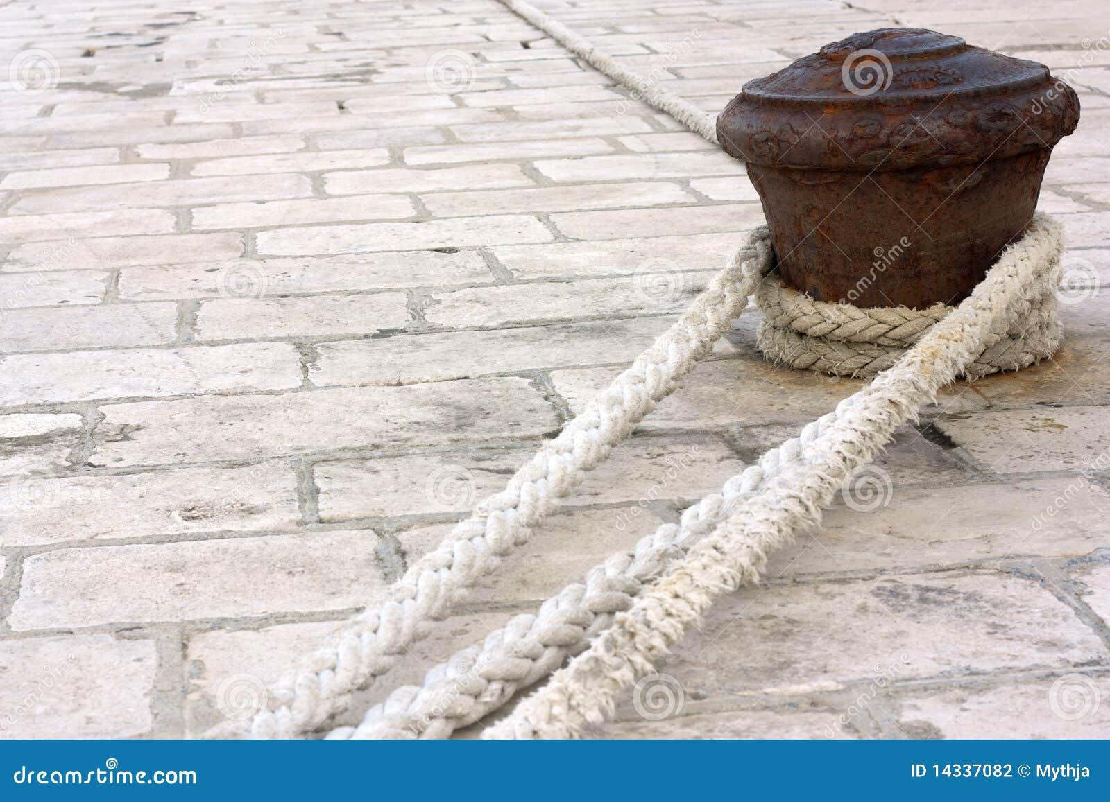 Roestige pijler met kabels.