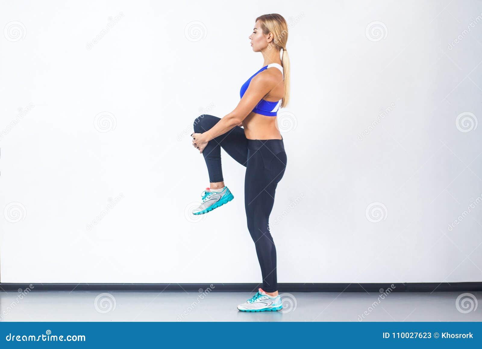 Rofile view blonde sporty woman, balancing on one leg