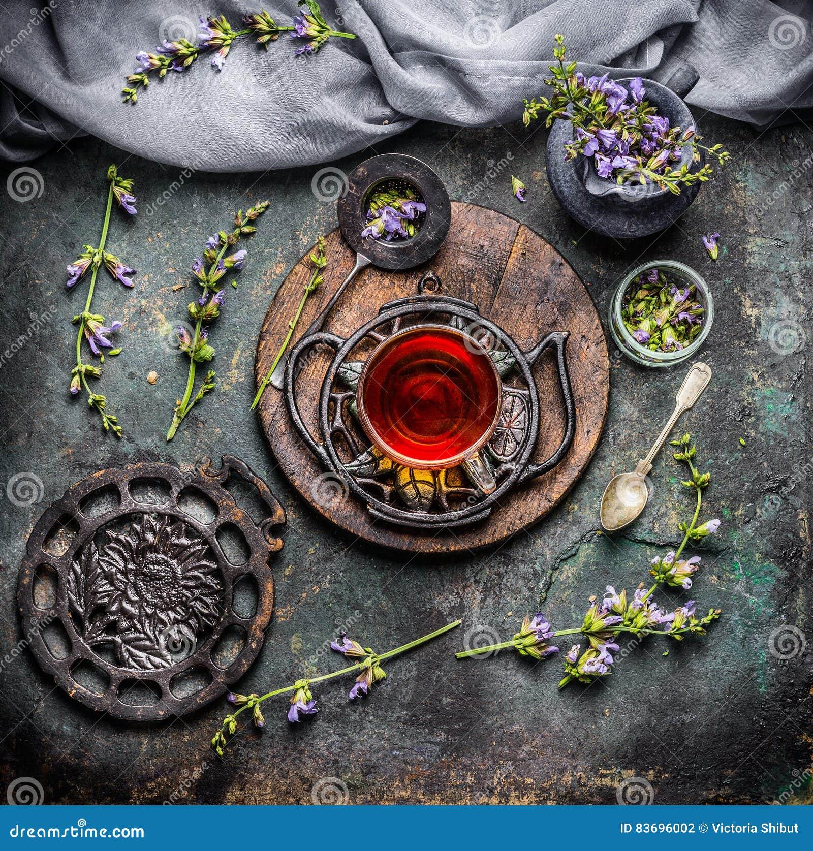 Rogivande kopp av örtte med nyast organiska ingredienser: örter och blommor på lantlig tappningbakgrund med tehjälpmedel