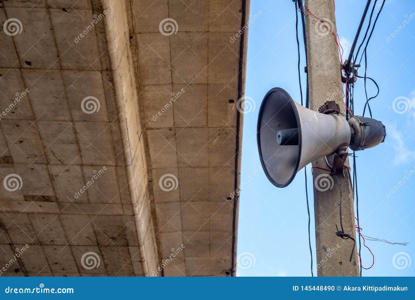 Rogu mówca na elektrycznym polityku z cementu niebieskiego nieba i mostu tłem