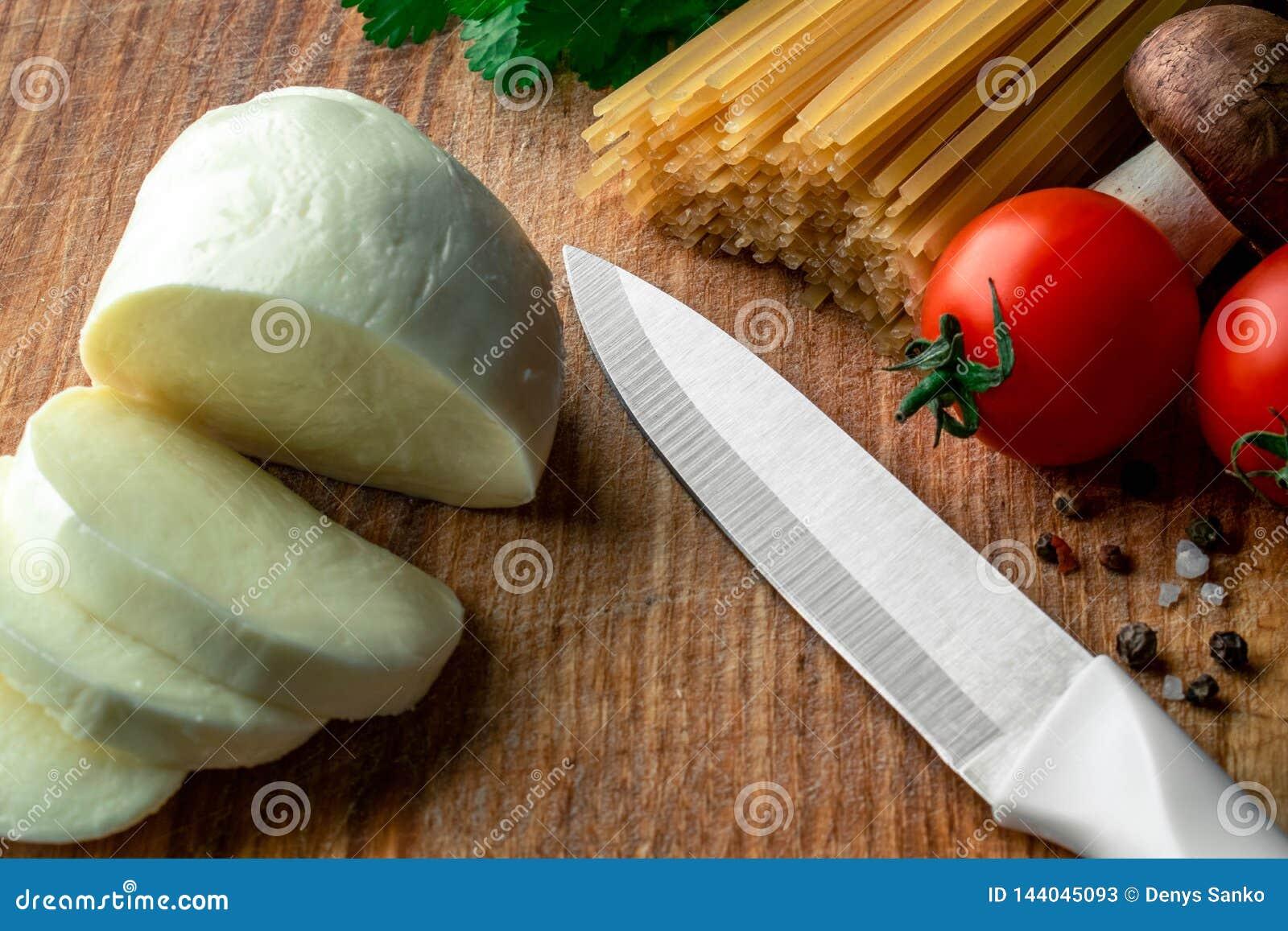Rohe Spaghettis auf einem hölzernen Brett mit geschnittenem Mozzarella, Frischgemüse, Gewürzen und Pilzen