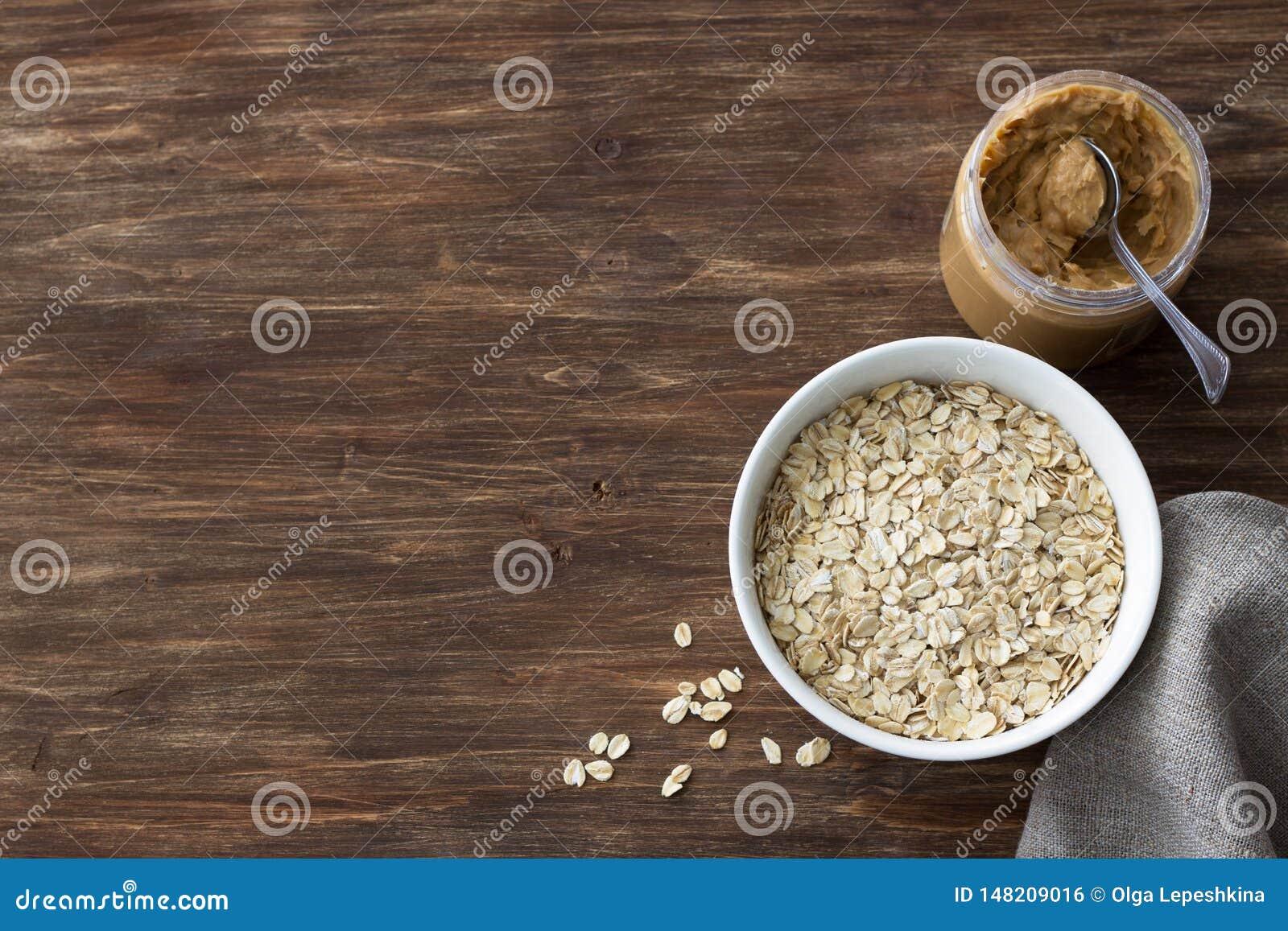 Rohes Hafermehl in einer weißen Schüssel mit Erdnussbutter, Bestandteile zum ein köstliches gesundes Frühstück auf einem hölzerne