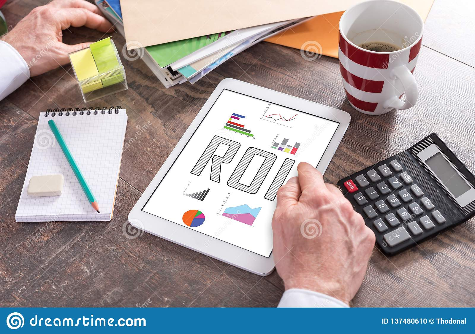 Roi concept on a tablet. Man using a tablet showing a roi concept stock photo