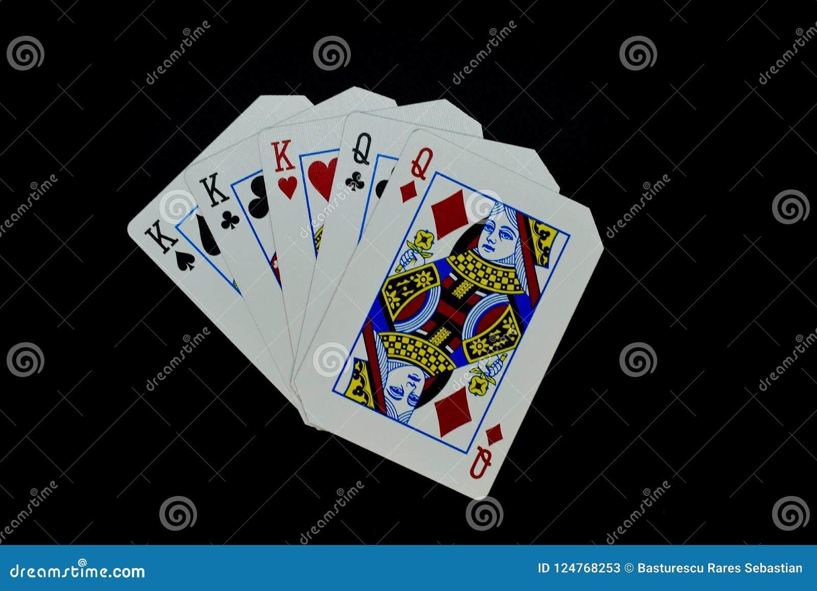 Rois de pleine maison au-dessus des cartes de reines en jeu de poker sur le fond noir