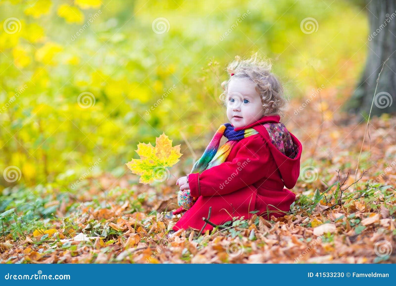 Rojo que lleva de la pequeña niña pequeña en capa del parque del otoño