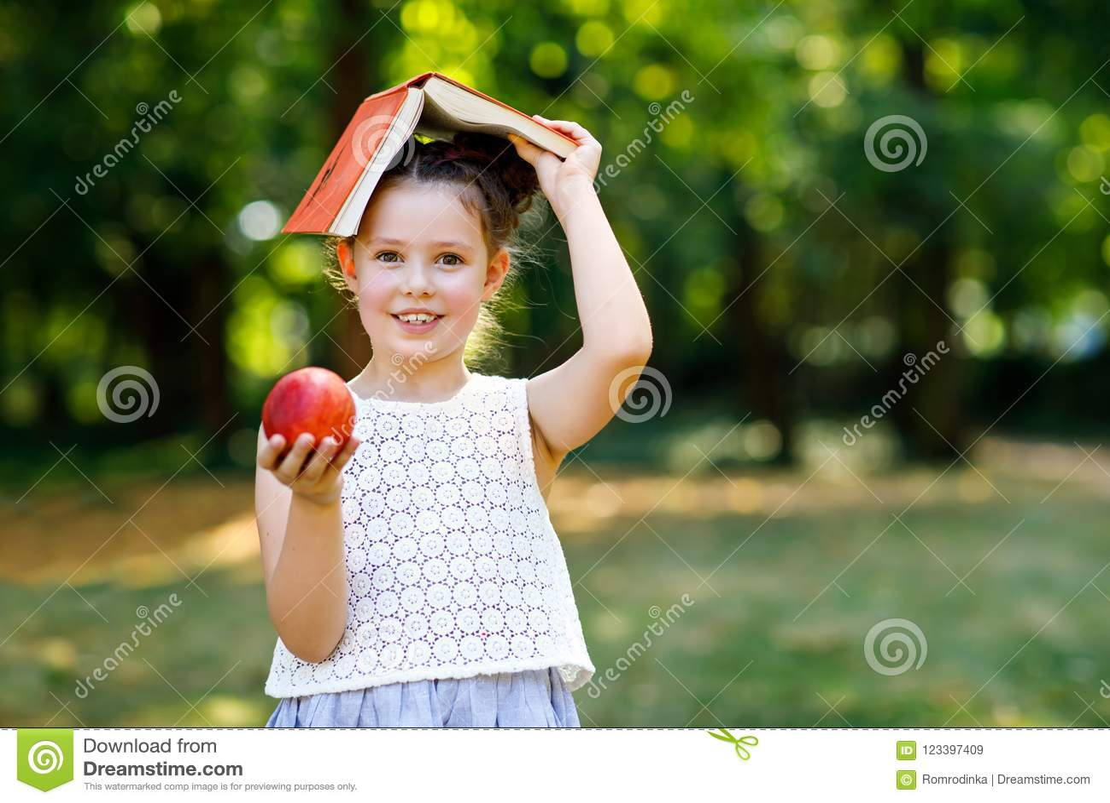 Rolig förtjusande flicka för liten unge med boken, äpplet och ryggsäcken på den första dagen till skolan eller barnkammaren Barn