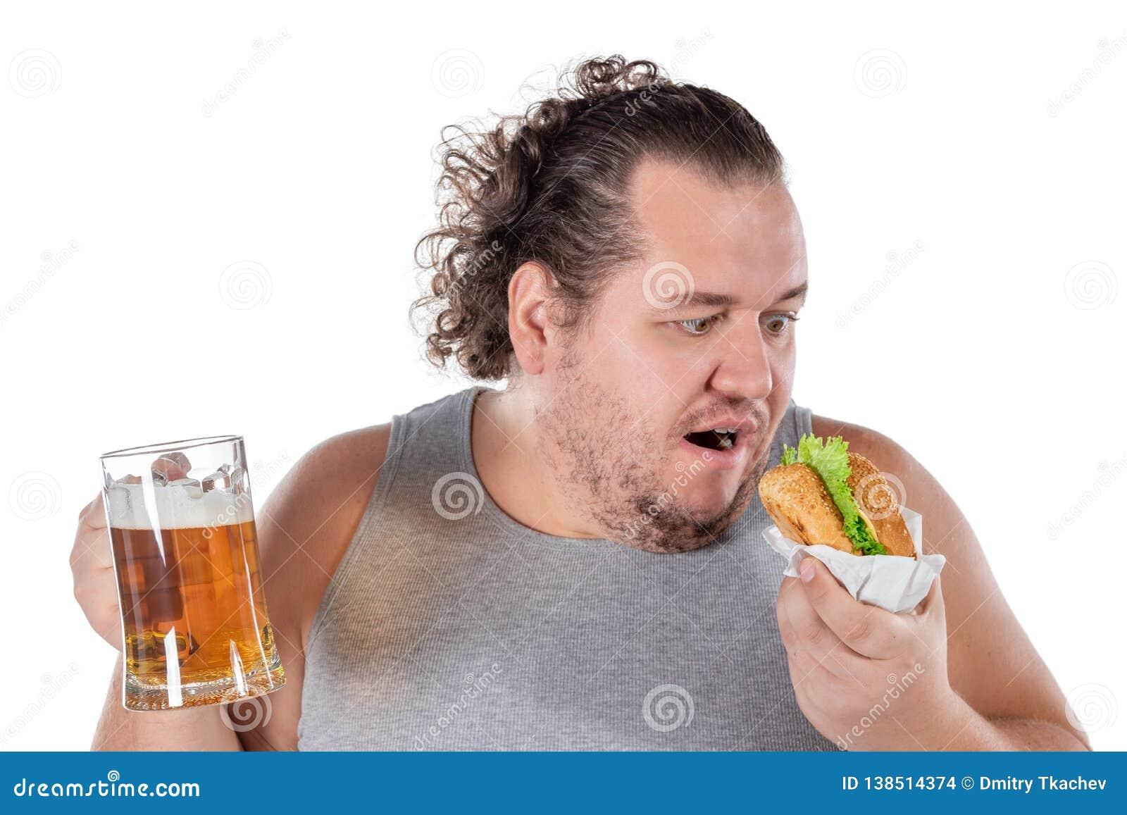 Rolig fet man som äter hamburgaren och dricker alkoholdrycken på vit bakgrund