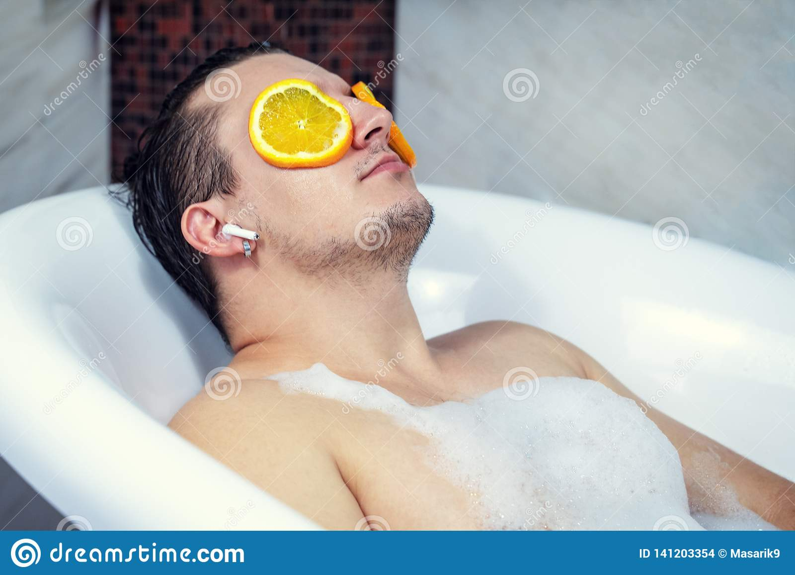 Rolig grabb som tvättar hans bad Lyssnar till musik med trådlös hörlurar Kopplat av från brunnsorttillvägagångssätt på framsida m